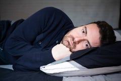 Mens met slaapwanorde die in het bed liggen royalty-vrije stock afbeelding