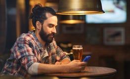 Mens met smartphone en bier het texting bij bar Stock Foto