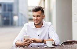 Mens met smartphone en koffie bij stadskoffie Royalty-vrije Stock Fotografie