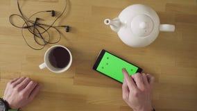 Mens met smartphone het drinken thee stock footage