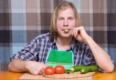 Mens met stuk van komkommer in de mond Royalty-vrije Stock Afbeeldingen