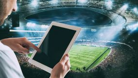 Mens met tablet bij het stadion om op het spel te wedden stock fotografie