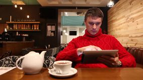 Mens met tabletcomputer het drinken thee in koffie stock video