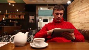 Mens met tabletcomputer het drinken thee in koffie stock videobeelden