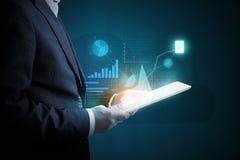 Mens met tabletpc die virtuele diagrammen analyseren Stock Afbeelding