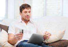 Mens met tabletpc en creditcard thuis Royalty-vrije Stock Foto