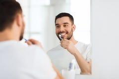 Mens met tandenborstel schoonmakende tanden bij badkamers Royalty-vrije Stock Foto's