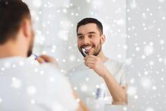 Mens met tandenborstel schoonmakende tanden bij badkamers stock afbeeldingen