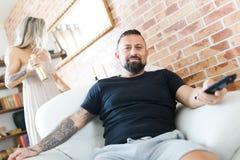 Mens met tatoegering het letten op televisiezitting in leunstoel - de vrouw onderzoekt spiegel stock fotografie