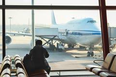 Mens met telefoon in de luchthavenzitkamer stock afbeeldingen