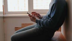 Mens met telefoon Onherkenbare jonge mens die in mobiele telefoonzitting op balkon dichtbij het venster babbelen stock footage