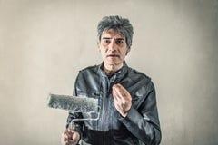 Mens met ter beschikking een rol aan verf stock foto