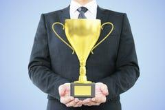 Mens met trofee blauwe achtergrond Royalty-vrije Stock Fotografie