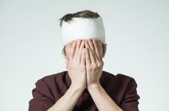 Mens met verband op zijn hoofd stock foto