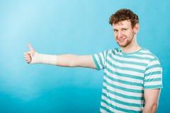 Mens met verbonden hand die duim tonen Stock Foto's