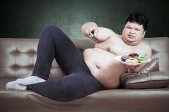 Mens met verre TV en donuts Stock Afbeeldingen