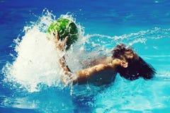 Mens met watermeloen in zwembad stock foto's