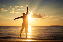 Mens met zijn handen omhoog in de zonsondergangtijd Stock Afbeeldingen