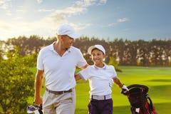 Mens met zijn zoonsgolfspelers die op golfcursus lopen stock foto
