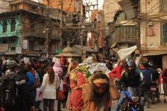 Mens met zware last in Katmandu, Nepal Stock Foto's