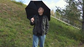 Mens met zwarte paraplu tijdens regen stock video