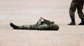 Mens in Militaire camouflagekleding en een masker die op zijn rug liggen het zand met machinegeweren in hand tijdens demonstratie royalty-vrije stock foto's