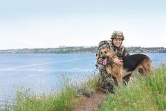 Mens in militaire eenvormig met Duitse herderhond Royalty-vrije Stock Foto