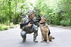 Mens in militaire eenvormig met Duitse herderhond stock foto