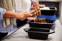 Mens Mobiel Controleren wordt geladen bij Luchthavenveiligheidscontrole royalty-vrije stock afbeelding