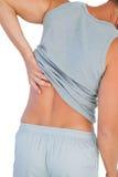 Mens in mouwloos onderhemd die aan lagere rugpijn lijden Stock Foto