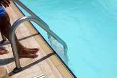 Mens neer aan het zwembad stock fotografie
