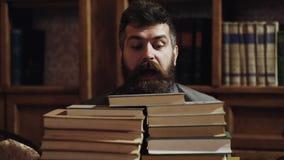 Mens, nerd op verrast gezicht tussen stapels van boeken in bibliotheek, boekenrekken op achtergrond Leraar of student met baard stock footage