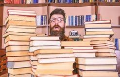 Mens, nerd op verrast gezicht tussen stapels van boeken in bibliotheek, boekenrekken op achtergrond Nerdconcept Leraar of stock afbeelding