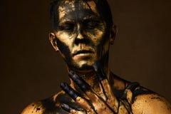 Mens omvat met gouden verf en zwarte ruwe olieverf stock foto