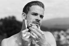 Mens omvat met schuim het scheren met scheermes Mannetje die met sexy sterke schouders zijn kin scheren stock foto's