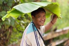 Mens onder banaanblad Stock Foto
