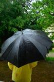 Mens onder de zwarte paraplu terwijl rainig Royalty-vrije Stock Foto