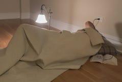 Mens onder deken op vloer Royalty-vrije Stock Fotografie
