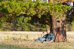 Mens onder een boom met een bijl Stock Foto's