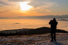 Mens op berg die foto's van lage stratus en zonsondergang nemen Royalty-vrije Stock Foto's