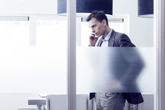 Mens op bureau mobiel uitnodigen Stock Afbeelding