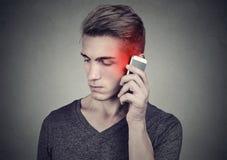 Mens op cellphone met hoofdpijn Verstoor ongelukkige kerel die op een telefoon spreken stock foto's