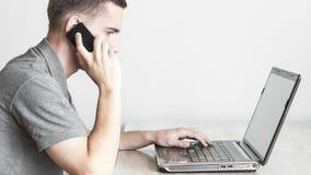 Mens op celtelefoon en computer Royalty-vrije Stock Afbeeldingen
