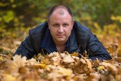 Mens op de achtergrond van de herfstbladeren Royalty-vrije Stock Afbeeldingen