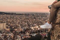 Mens op de bovenkant van een berg die op de stad letten royalty-vrije stock foto's