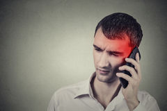 Mens op de telefoon met hoofdpijn Cellulair mobiel stralingsconcept stock afbeeldingen