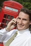 Mens op de Telefoon van de Cel in Londen met Rode Telefooncel Stock Foto's