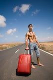 Mens op de weg met zijn koffer Stock Foto