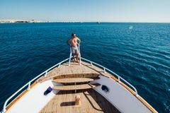 Mens op een jacht Mooie mening van een boog van een jacht bij zeewaarts sailing Rijen van luxejachten bij jachthavendok De zomerv royalty-vrije stock afbeeldingen