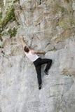 Mens op een rotsmuur Stock Foto's